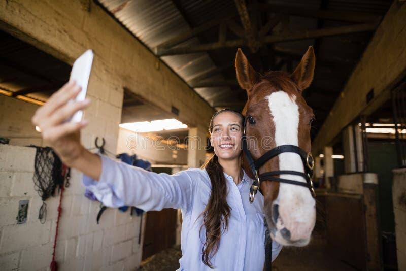 Uśmiechnięty weterynarz bierze selfie z koniem w stajence fotografia stock