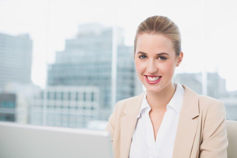 Uśmiechnięty wspaniały bizneswoman pracuje na jej laptopie fotografia stock