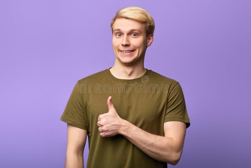 Uśmiechnięty wspaniały mężczyzna z kciukiem w górę pozować kamera fotografia royalty free