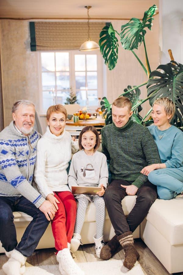 Uśmiechnięty wspaniały rodzinny obsiadanie na leżance z laptopem zdjęcia stock