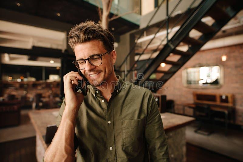 Uśmiechnięty wykonawczy opowiadać na telefonie komórkowym w biurze fotografia stock