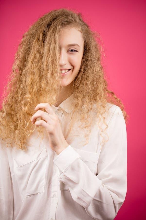 Uśmiechnięty wzorcowy macanie jej kędzierzawy blondyn obrazy royalty free
