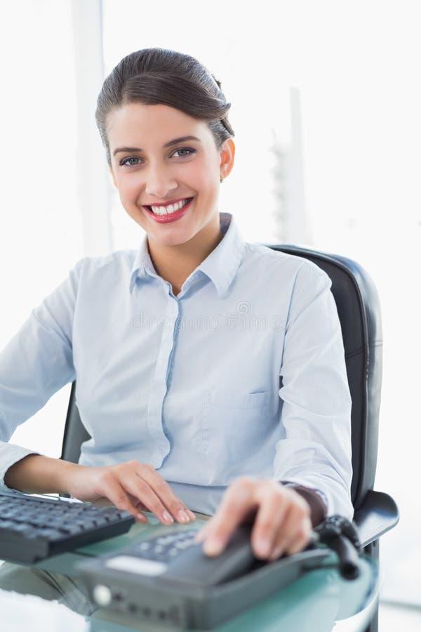Uśmiechnięty z klasą brown z włosami bizneswoman wiesza w górę telefonu fotografia stock