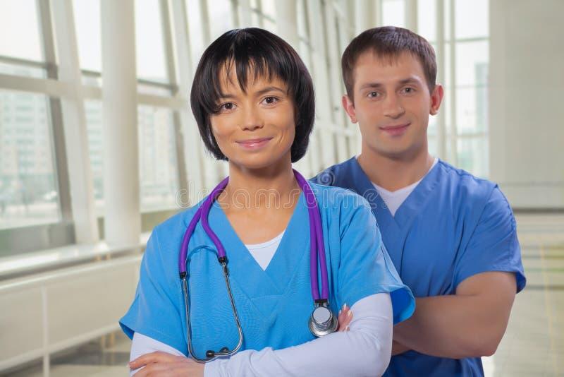 Uśmiechnięty zaopatrzenie medyczne mężczyzna, kobieta z krzyżować rękami patrzeje i obrazy royalty free
