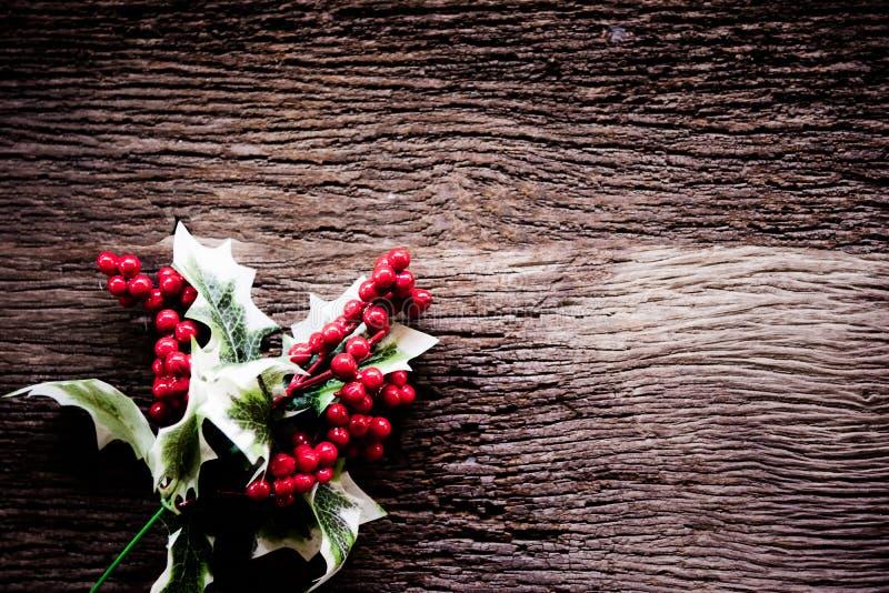 Uświęcona jagoda opuszcza Bożenarodzeniową dekorację na starym drewnianym tle, rocznika brzmienie obrazy stock