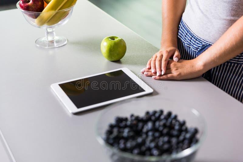 Używać cyfrową pastylkę w kuchni zdjęcia stock