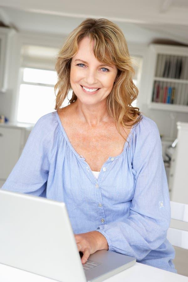 Używać laptop w połowie pełnoletnia kobieta zdjęcia stock
