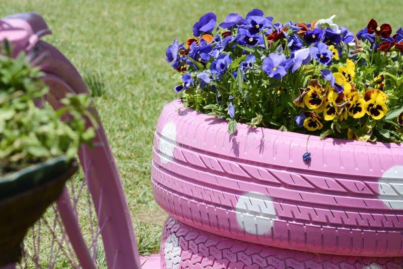 Używać opona kwiatu kosz obraz stock