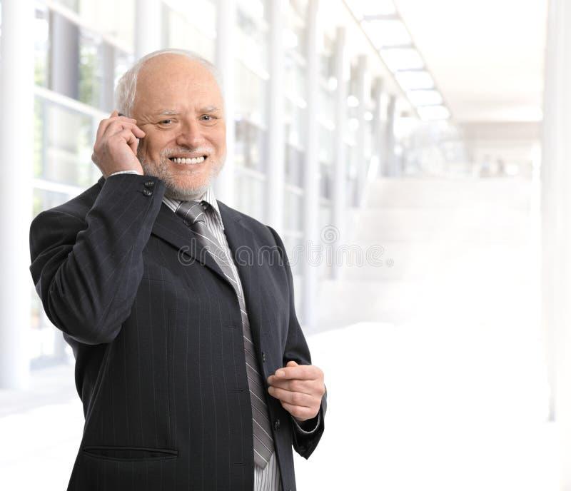 Używać telefon komórkowy uśmiechnięty biznesmen zdjęcie stock