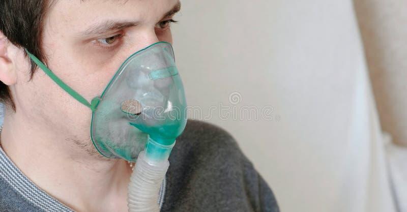 Używa nebulizer i inhalator dla traktowania Zbliżenie młodego człowieka ` s twarz wdycha przez inhalator maski Boczny widok obraz stock