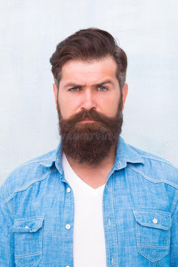u Хипстер с бородой и усик носят рубашку джинсовой ткани Зверский красивый человек хипстера на серой стене стоковые изображения