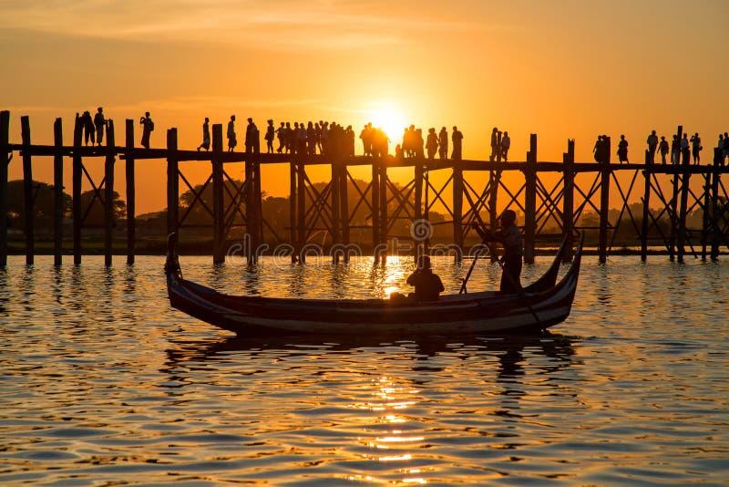 U Bein桥梁的现出轮廓的人在日落, Amarapura, Mandal 免版税图库摄影