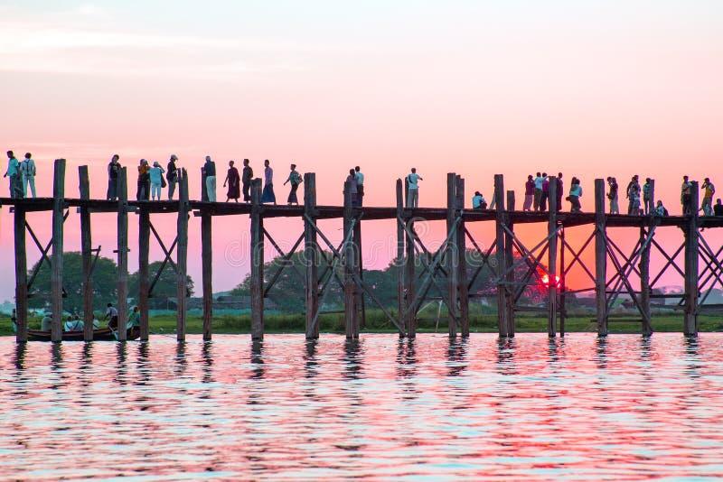 U Bein桥梁的现出轮廓的人在日落, Amarapura, Mandal 免版税库存照片