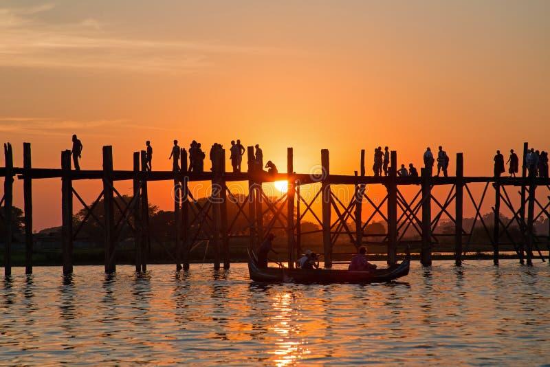 U Bein桥梁的现出轮廓的人在缅甸的日落 库存图片