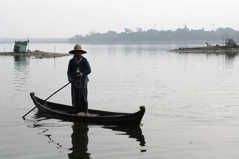 U-BEIN BRIDGE/AMARAPURA, MYANMAR 22 DE ENERO DE 2016: Una mujer está navegando su barco en el lago Taungthaman que está siendo cr imagenes de archivo