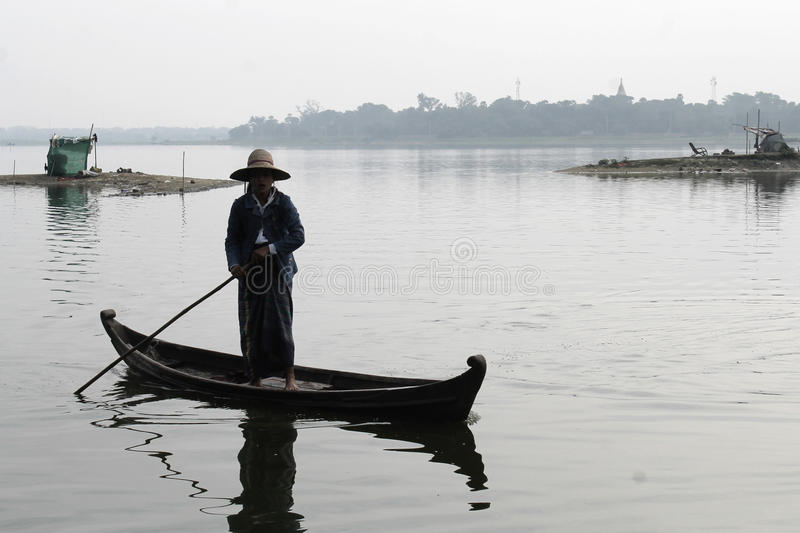 U-BEIN BRIDGE/AMARAPURA, MYANMAR JAN 22, 2016: A woman is navigating her boat on the Taungthaman Lake that is being crossed by the stock images