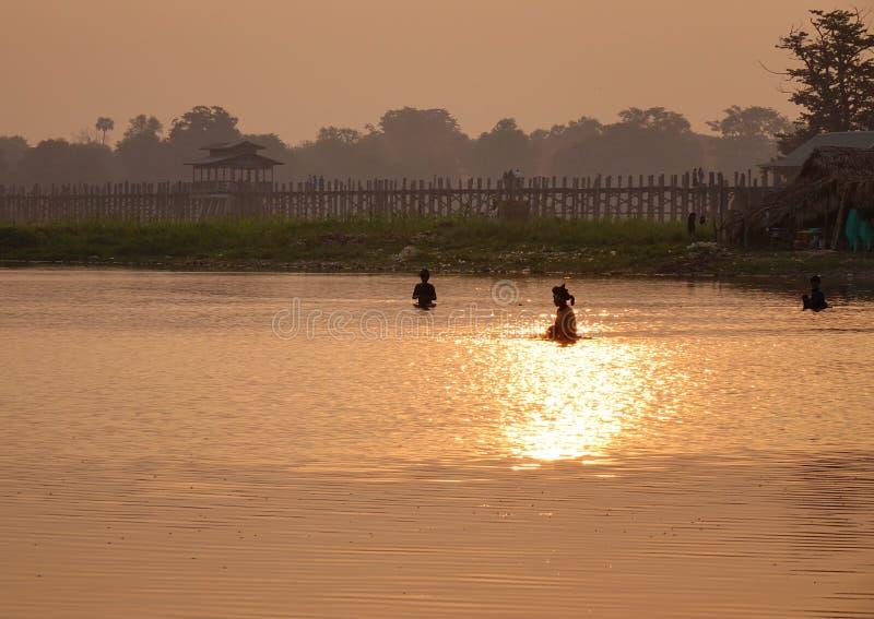 U Bein Bridge in Mandalay, Myanmar. Fishermen on the lake near U Bein Bridge at sunrise in Mandalay, Myanmar. U Bein Bridge has become one of Myanmar iconic royalty free stock photography