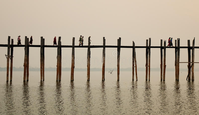 U Bein Bridge in Mandalay, Myanmar. People walking on U Bein Bridge at sunrise in Mandalay, Myanmar. U Bein Bridge is believed to be the oldest and longest royalty free stock image