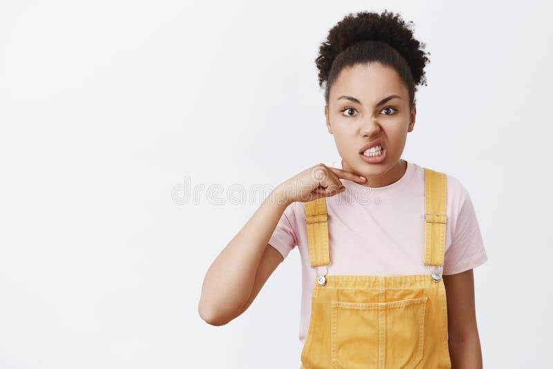 U bent deadman Portret die van boze boze donker-gevilde jonge vrouwelijke student in gele overall, duim boven gezicht houden royalty-vrije stock fotografie