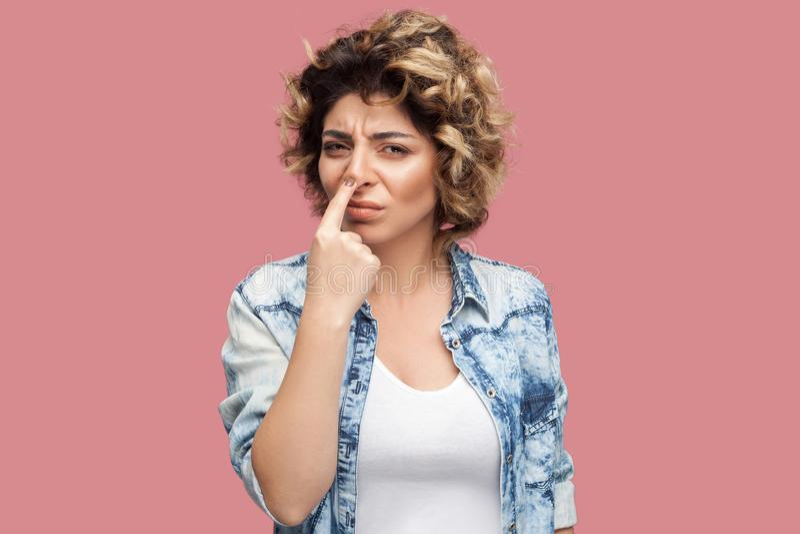 U bent leugenaar Portret van ernstige jonge vrouw met krullend kapsel in toevallig blauw overhemd die zich met vinger op haar neu royalty-vrije stock afbeeldingen
