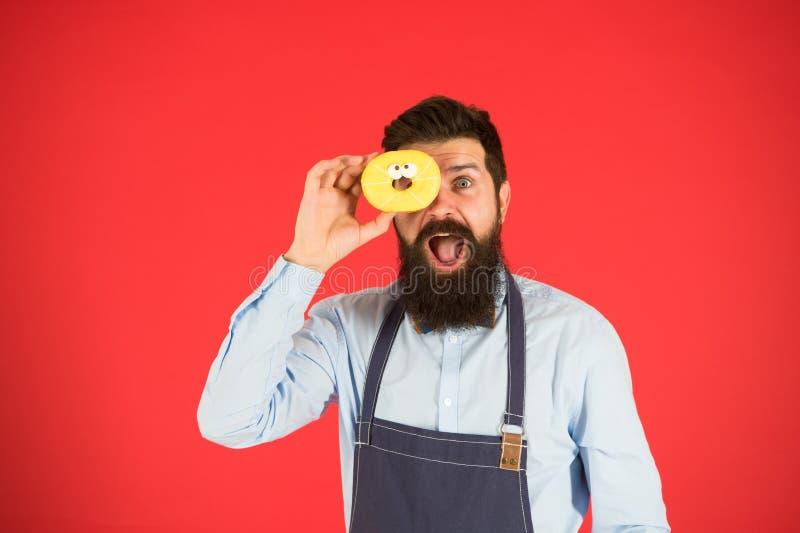 U bent wat u eet Baker greepdoughnut Grappige hipster Gebaarde mensenkok Chef-kokmens in koffie Dieet en gezond voedsel royalty-vrije stock foto