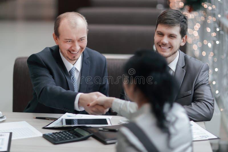 U?cisku d?oni klient w nowo?ytnym biurze i kierownik obrazy stock