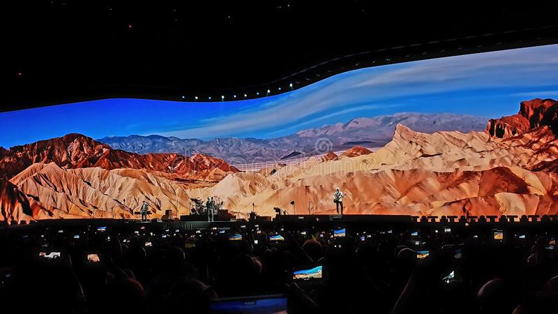 U2 concert. Distant perspective of U2 in concert including darkened audience with mountain landscape behind stage on the Joshua Tree tour in 2017 stock image