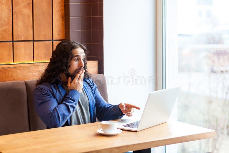 U die kidding! Verraste jonge volwassen mens freelancer in toevallige stijlzitting in koffie en het spreken met vrienden in lapto stock foto's