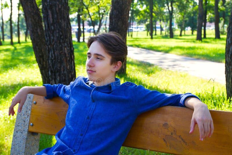 ?u?eres Portr?t des jungen Mannes im Park Jugendlicher, der Rest im Park auf der Bank hat stockfoto