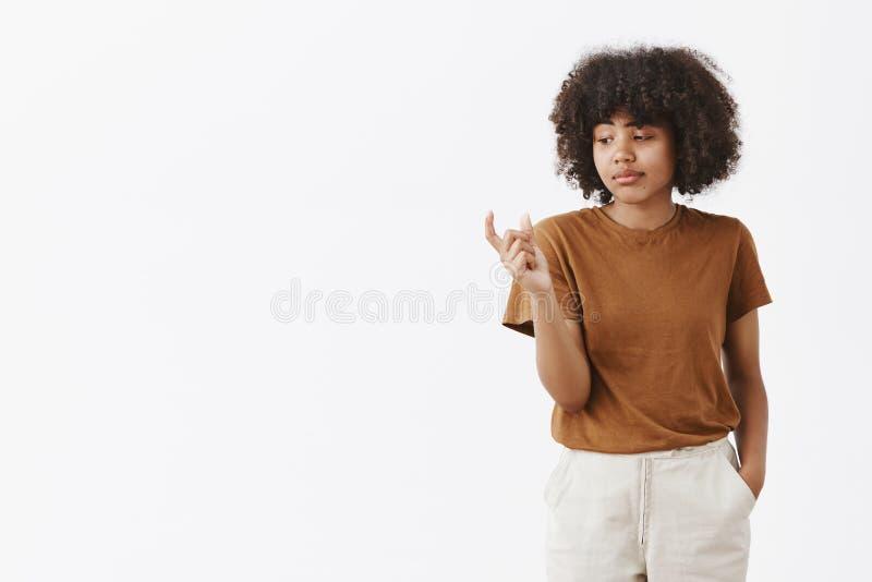 U kall het grootte Niet onder de indruk zijnde achteloze en onverschillige leuke Afrikaanse Amerikaanse vrouwelijke student met a stock fotografie