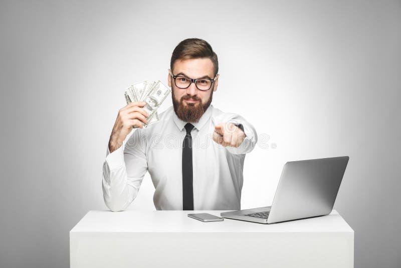 U kunt geld verdienen! Portret die van knappe tevreden gebaarde jonge werkgever in witte overhemd en avondkledingzitting in burea stock afbeelding