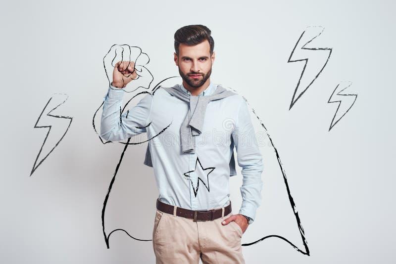 U kunt het doen! Jonge aantrekkelijke donkerbruin dragend een getrokken kaap en opheffend één hand clanched in vuist boven zijn h stock afbeeldingen