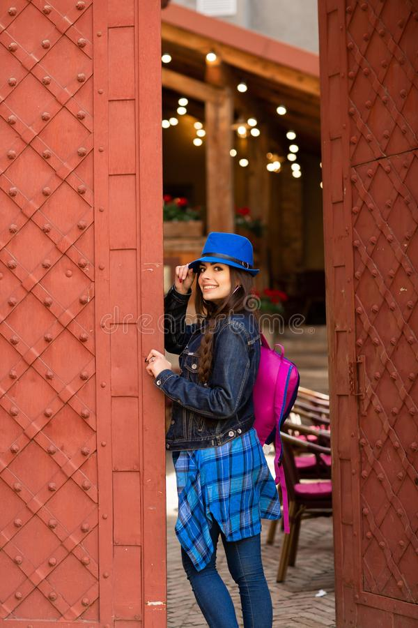 U?miechni?ta ?adna dziewczyna w b??kitnym kapeluszowym pobliskim starym budynku z antykwarskimi czerwonymi drzwiami kobiety model zdjęcia royalty free