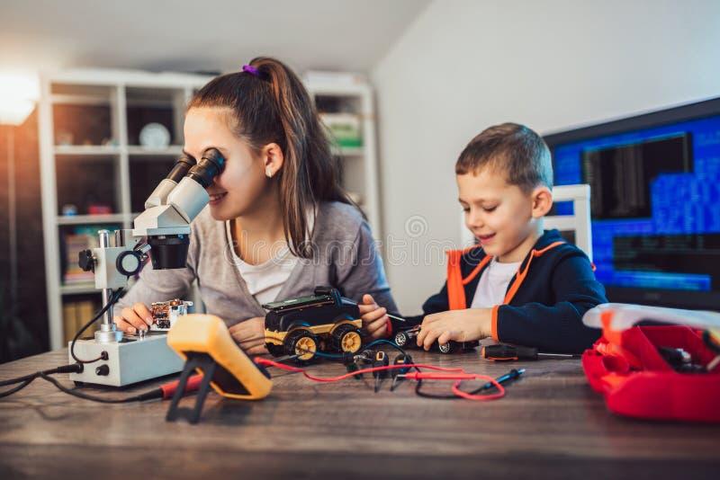 U?miechni?ta ch?opiec i dziewczyny konstrukcji techniczna zabawka i robi robotowi Techniczna zabawka na sto?owy pe?nym szczeg??y obraz royalty free