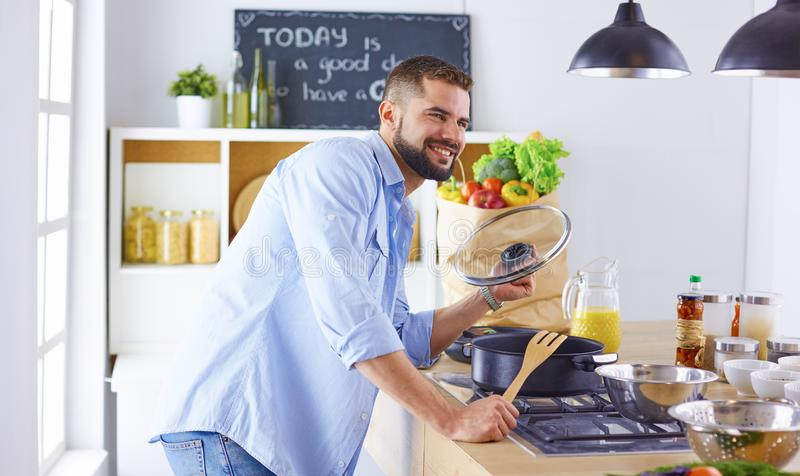 U?miechni?ta i ufna szef kuchni pozycja w wielkiej kuchennej degustacji gotuj?cy naczynie zdjęcie stock