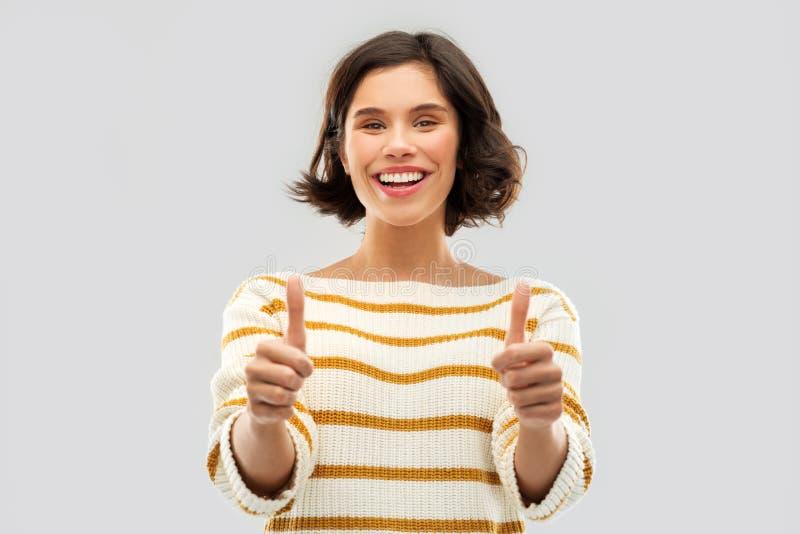 U?miechni?ta kobieta w pulowerze pokazuje aprobaty zdjęcia stock