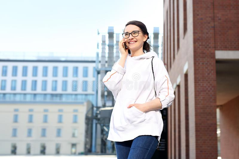 U?miechni?ta naturalna m?oda kobieta opowiada na telefonie fotografia royalty free