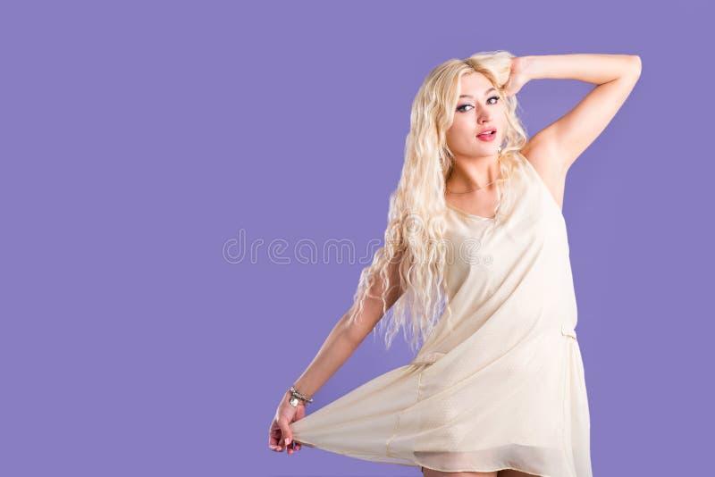 U?miechni?ta pi?kna blondynki kobieta na fio?kowym tle obraz royalty free
