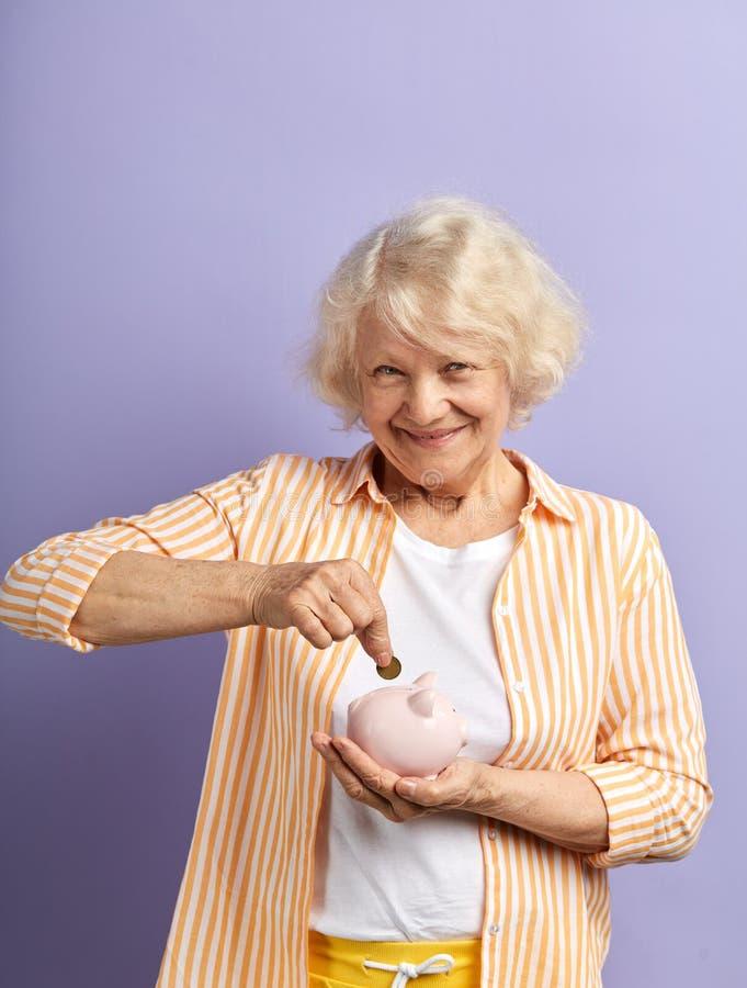 U?miechni?ta starsza kobiety oszcz?dzania euro moneta w piggybank i ono u?miecha si? przy kamer? zdjęcie stock