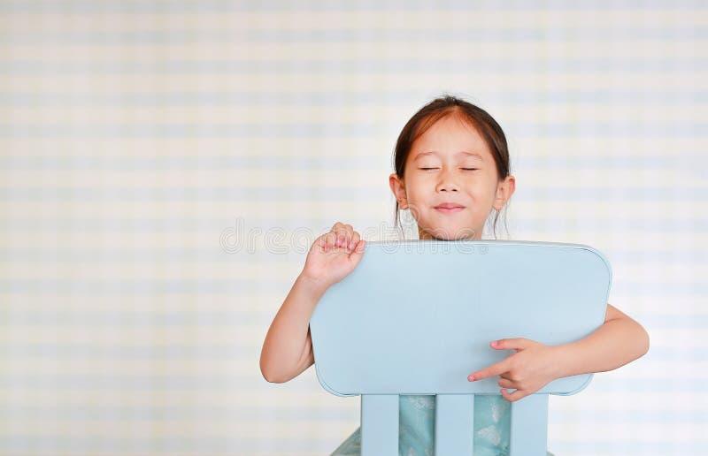 U?miechni?tego ma?ego Azjatyckiego dziecka preschool dziewczyna w dziecina pokoju pozach na plastikowym dziecka krze?le zdjęcie royalty free