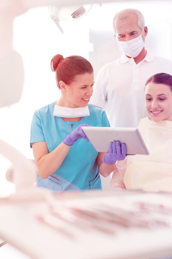 U?miechni?ty dentysta dyskutuje z pacjentem nad cyfrow? pastylk? przy stomatologiczn? klinik? zdjęcie royalty free