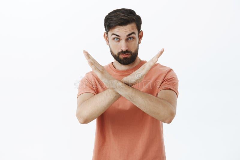 U moet ophouden Portret van ernstige en zekere gebaarde mannelijke vriend die kruis met handen het maken niet en verbod tonen stock afbeeldingen