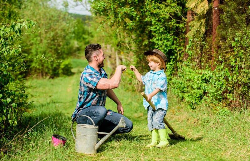 u r πατέρας και γιος στο καπέλο κάουμποϋ στο αγρόκτημα το πότισμα χρήσης μπορεί και δοχείο στοκ φωτογραφία με δικαίωμα ελεύθερης χρήσης