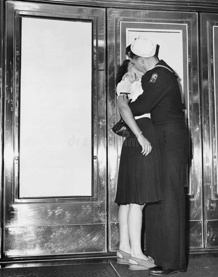 U S 水手和他的女朋友庆祝战争的结尾的新闻与日本的在平方纽约的时间的跨勒克斯剧院前面 免版税库存照片