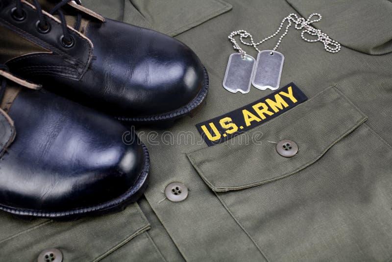 U S Armee-Niederlassungs-Band mit Erkennungsmarken und Stiefeln auf Olivgrünuniform lizenzfreie stockfotografie