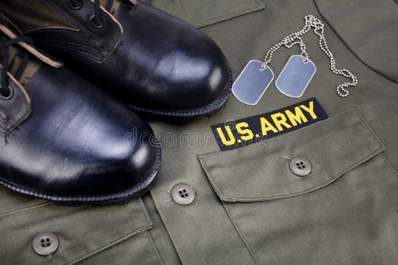 U S Armee-Niederlassungs-Band mit Erkennungsmarken und Stiefeln auf Olivgrünuniform lizenzfreies stockbild