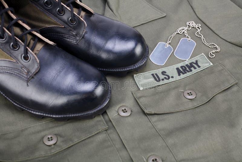 U S Armee-Niederlassungs-Band mit Erkennungsmarken und Stiefeln auf Olivgrünuniform stockfotografie