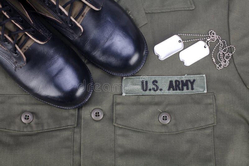 U S Armee-Niederlassungs-Band mit Erkennungsmarken und Stiefeln auf Olivgrünuniform stockfoto