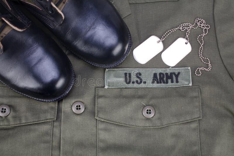 U S Armee-Niederlassungs-Band mit Erkennungsmarken und Stiefeln auf Olivgrünuniform stockbild