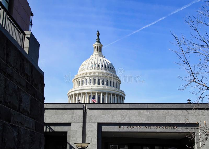 U.S. Capitol Visitor`s Center with flying American Flag and bronze Statue of Freedom topping the dome. royalty free stock photo